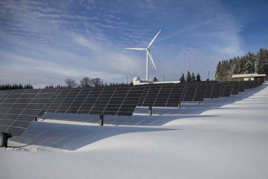 solar panels utility in the snow with wind turbine